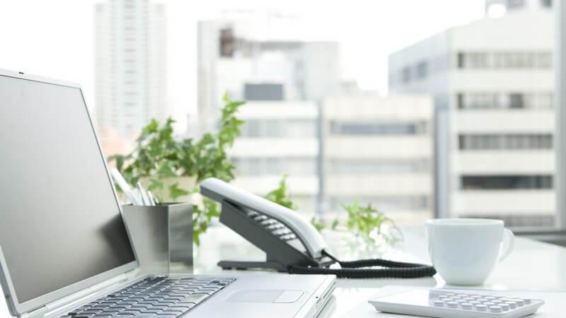 Schreibtisch im Büro mit Laptop, Telefon, Notizblock, Kaffeebecher