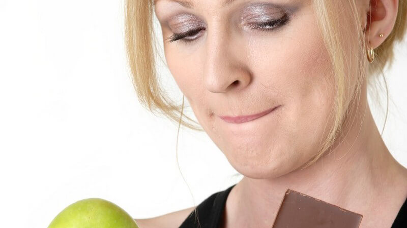 Frau hält Apfel und Schokolade in Händen, muss sich entscheiden