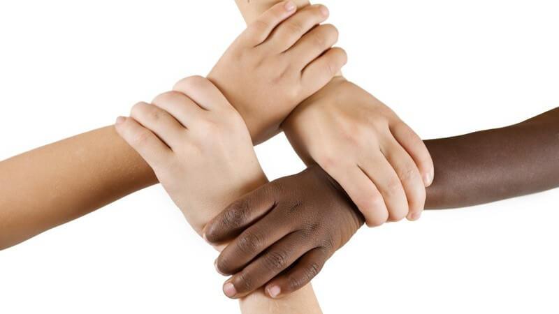 Drei weiße und eine schwarze Kinderhand halten sich gegenseitig am Handgelenk fest