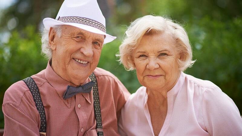 Modisch gekleidetes, lächelndes Seniorenpaar, Mann mit Fliege, Hut und Hosenträgern