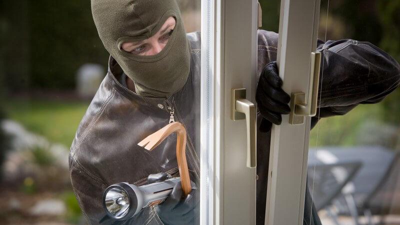 Mann mit grüner Maske bricht Balkontür auf