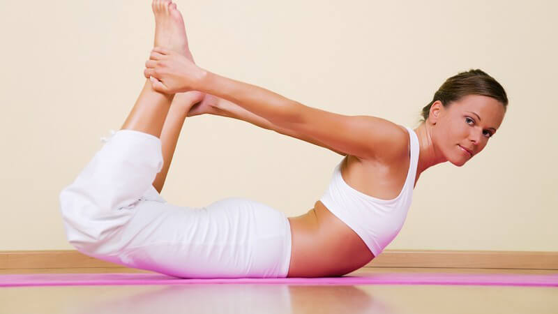 Yoga - Junge Frau liegt wippend auf dem Bauch und zieht die Beine an