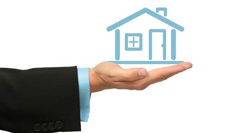 Ausgestreckter Männerarm, offene Hand, darauf blau gemaltes Haus