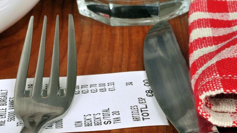 Rechnung liegt auf dem Tisch eines Restaurants unter Besteck
