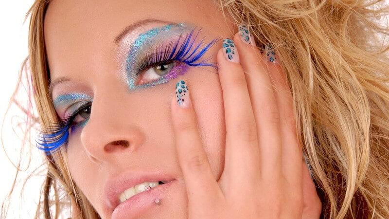 Blonde Frau mit bunten Wimpern, Lidschatten und bunten Nägeln