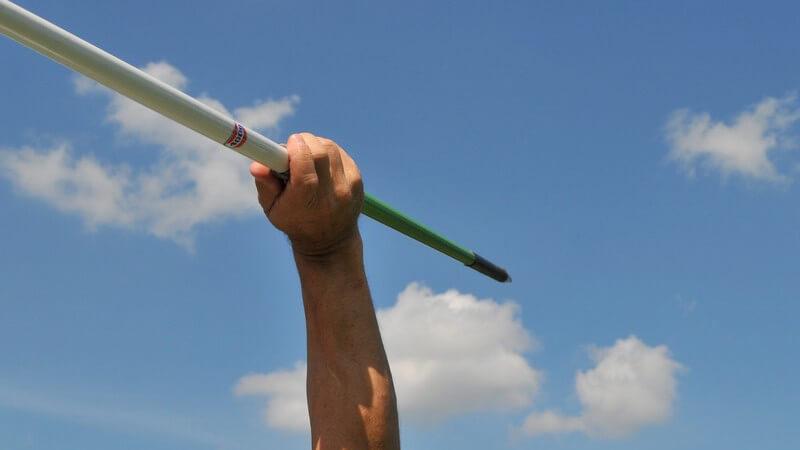 Arm beim Speerwurf unter blauem Himmel