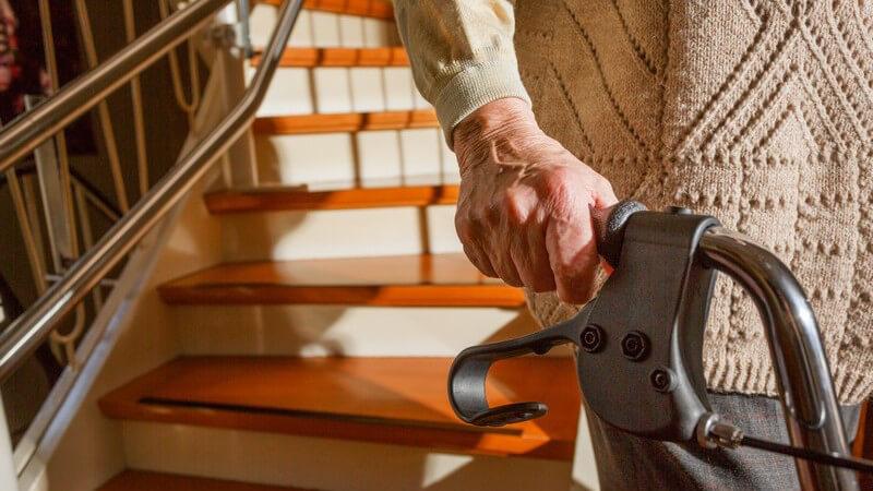 Hand einer alten Frau am Rollator, im Hintergrund Treppe ihrer Wohnung
