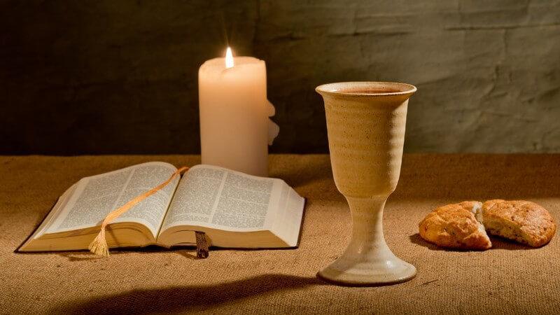 Religion des Christentums: aufgeschlagene Bibel, Brot und Abendmahlskelch mit Wein