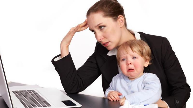 Gestresste Geschäftsfrau beim Arbeiten am Laptop, auf ihrem Schoß sitzt ein weinendes Kind