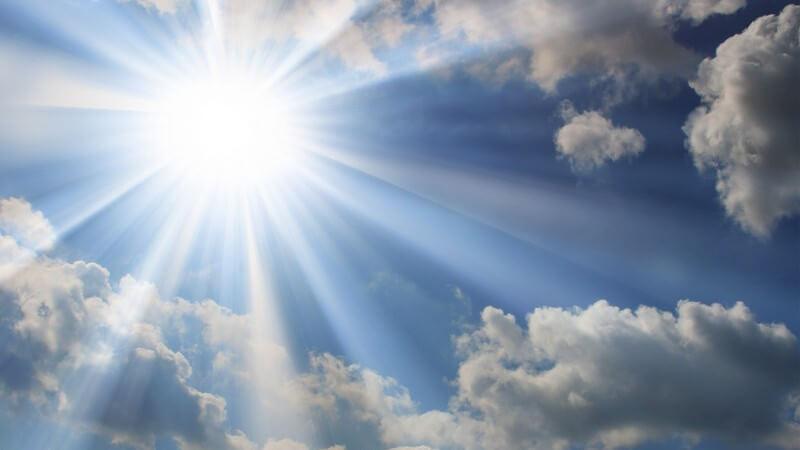 Strahlender Sonnenschein an blauem Himmel bricht durch Wolken
