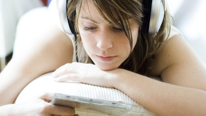 Nahaufnahme junge Frau liegt auf Couch, hört Musik über Kopfhörer