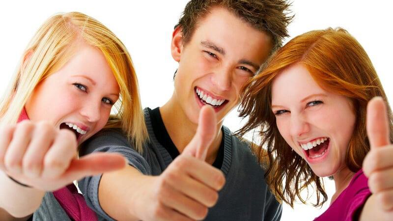 Drei Jugendliche lachen und halten Daumen in Kamera