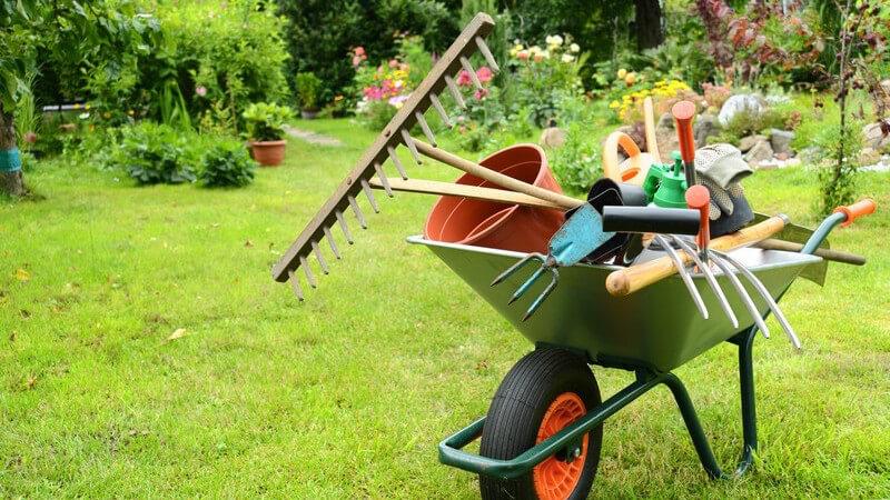 Gartenarbeit - Schubkarre mit Harken, Blumentöpfen, Gießkanne, Schaufel und Handschuhen