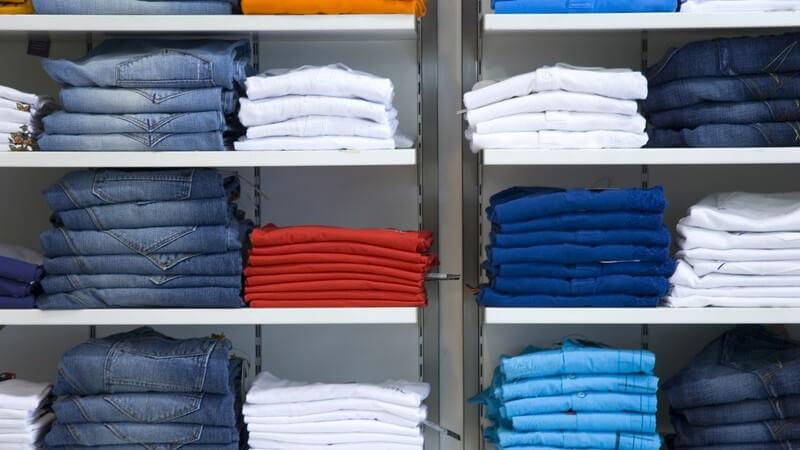 Regal mit gestapelten Jeans und bunten Hosen