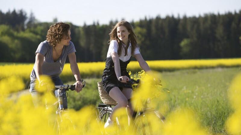 Junges Paar fährt mit Fahrrädern durch Felder