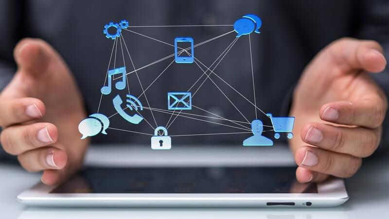 Hände eines Geschäftsmanns über einem Tablet, darüber moderne Mediensymbole, Kommunikation