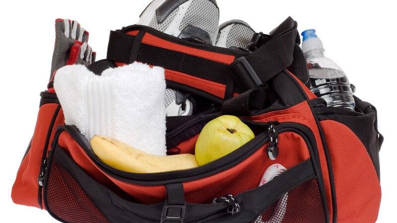 Gepackte Sporttasche mit Sportschuhen, Getränk, Handtuch, Obst