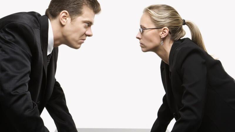 Frau und Mann mit bösem Gesichtsausdruck stehen sich gegenüber, Hände auf Tischplatte