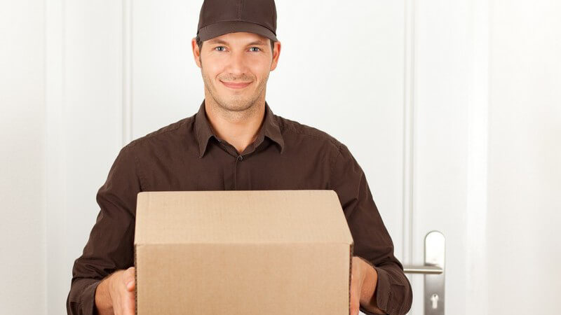 Postbote liefert Paket vor Haustür