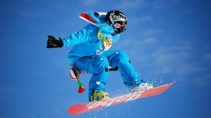 Snowboarder im Sprung vor blauem Himmel