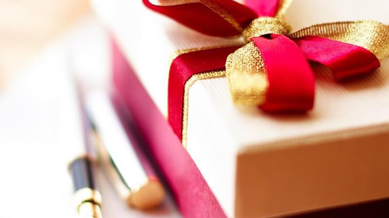 Nahaufnahme Geschenkschachtel, daneben liegt Füller