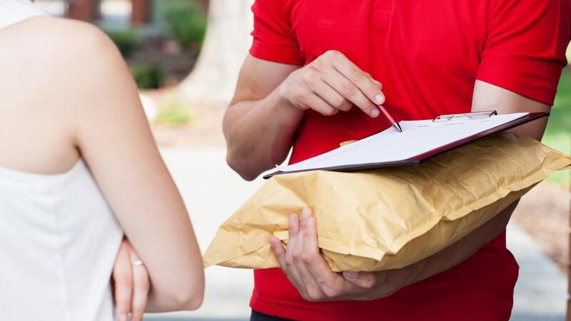 Paketdienst - Postbote bringt Päckchen und bittet um Unterschrift