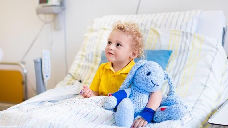 Kleiner Junge in gelbem Poloshirt sitzt mit seinem blauen Kuscheltier im Krankenhausbett