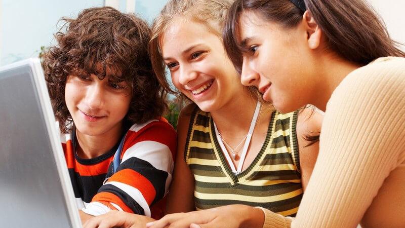 2 Mädchen, 1 Junge schauen auf einen Laptop