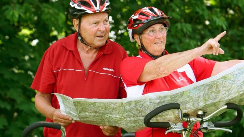 Senioren Paar auf Fahrradtour, schauen auf Karte den Weg nach