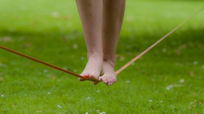 Füße balancieren auf Slackline-Seil über Wiese