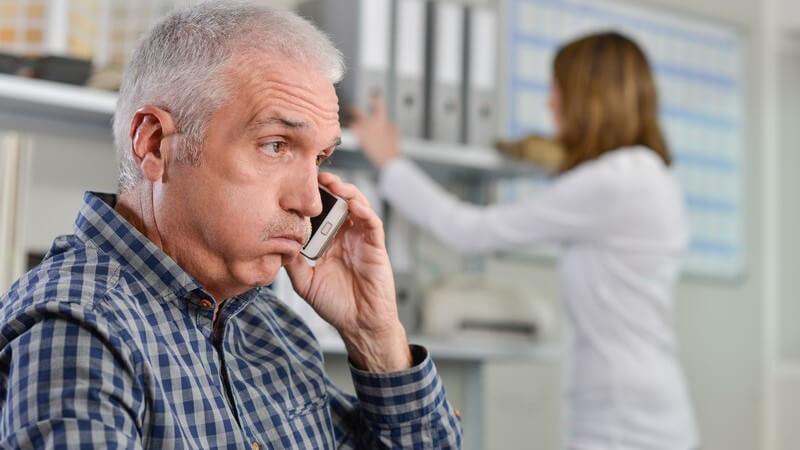 Mann mit grauen Haaren telefoniert im Büro mit dem Smartphone und guckt gestresst, im Hintergrund steht eine Kollegin