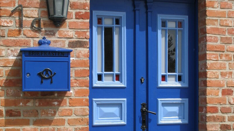 Blaue Eingangstür an Backsteinhaus, daneben blauer Briefkasten