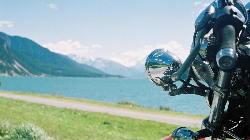 Ausschnitt Motorrad vor Gebirgslandschaft mit See