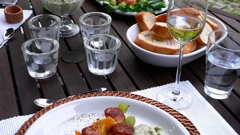 Gedeckter Gartentisch mit Grillspießen, Brot und Dip
