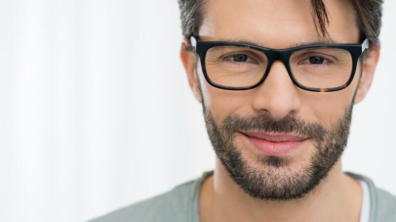 Portrait eines sympathischen jungen Mannes mit dunklen Haaren, Dreitagebart und Hornbrille
