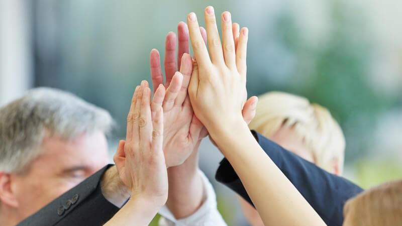 High Five für Erfolg im Beruf - Mitarbeiter in Geschäftskleidung klatschen ab