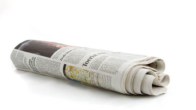Zusammengerollte, niederländische Zeitung auf weißem Hintergrund