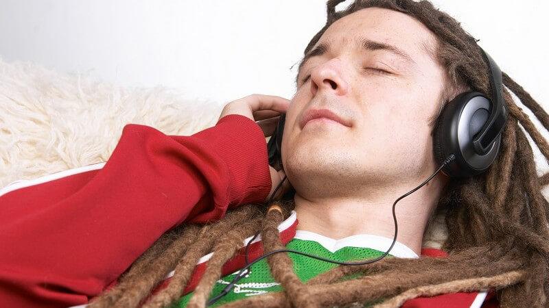 Junger Mann mit Rastalocken oder Dreadlocks und großen Kopfhörern liegt auf dem Boden auf einem Schaffell und hört Musik
