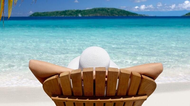 Urlauber mit Strohhut auf Sonnenliege unter Palmen mit Aussicht auf das Meer