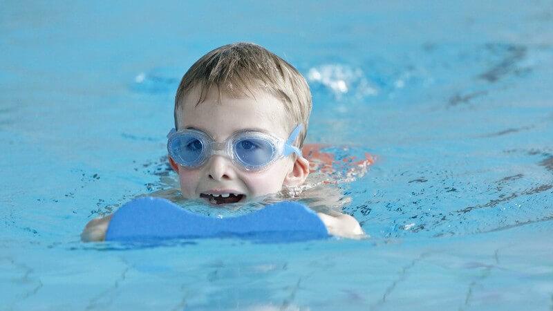 Kleiner Junge mit Taucherbrille und Schwimmhilfe im Wasser
