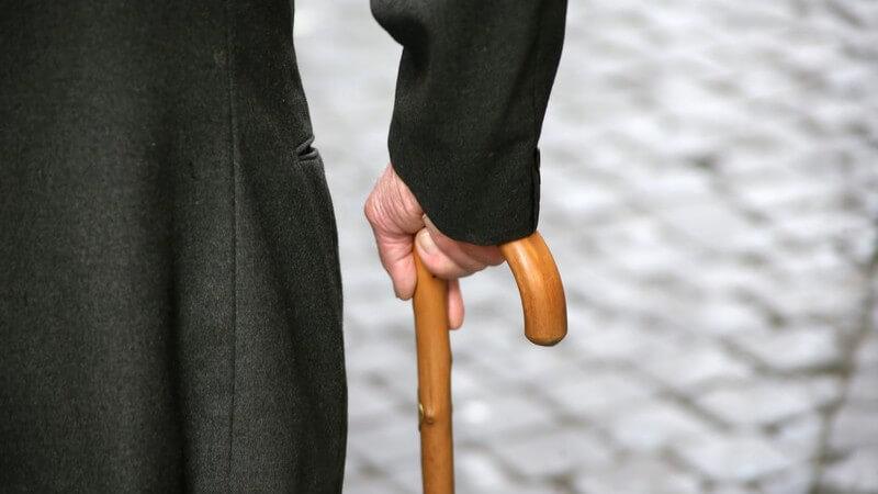 Rückansicht Körperausschnitt alter Mann mit Gehstock auf Straße