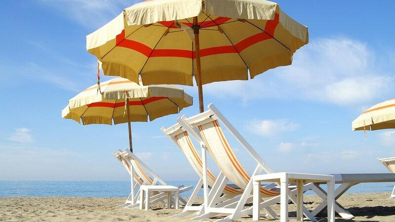 Liegen mit Sonnenschirmen auf Sandstrand, im Hintergrund Meer
