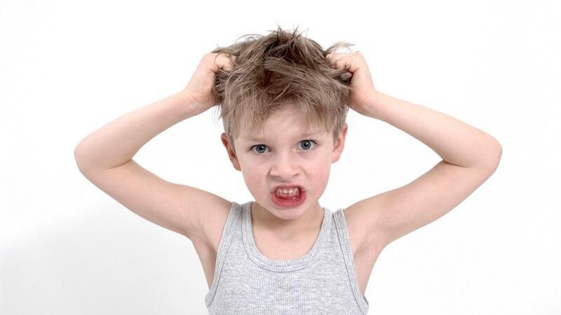 Kleiner Junge mit verärgertem Blick greift sich in Haare