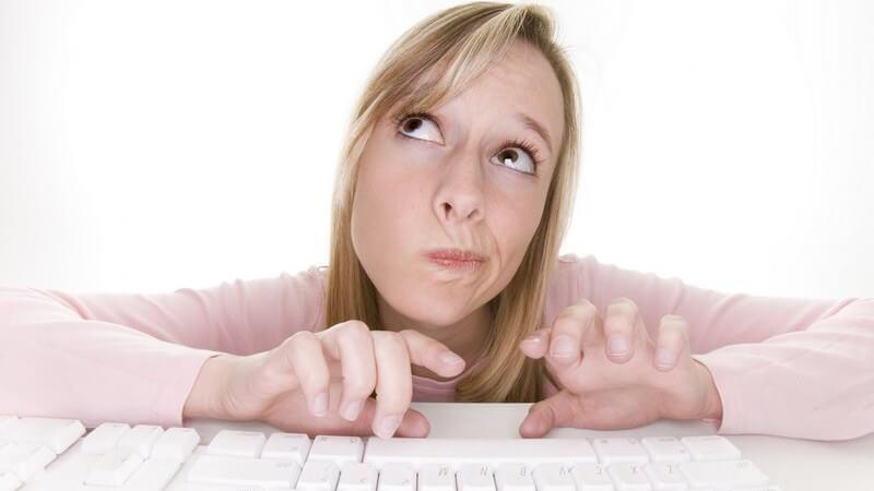 Junge Frau vor Computertastatur, schaut nachdenklich nach oben