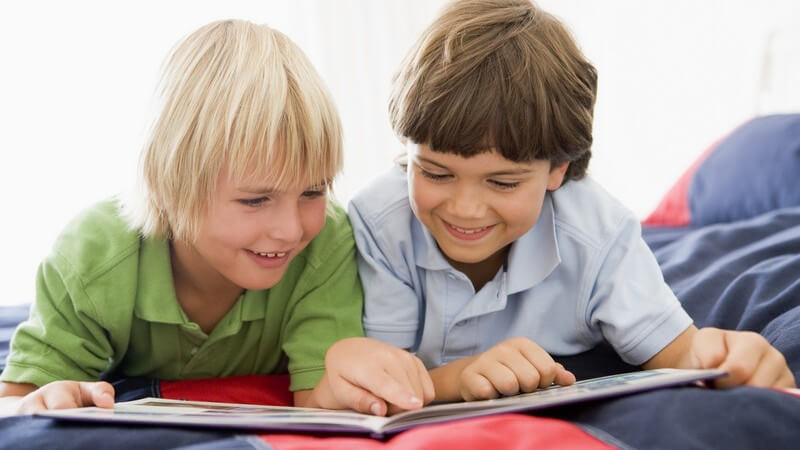 Zwei befreundete Jungen liegen lächelnd auf Bett und schauen sich gemeinsam ein Buch an