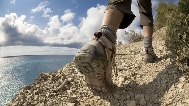 Frauenfüße mit Wanderschuhen wandern auf Klippe am Meer
