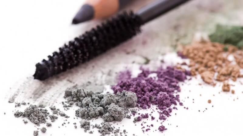 Lidschattenbrösel in grau, lila, orange und grün, dahinter Mascarabürste und Kajalstift