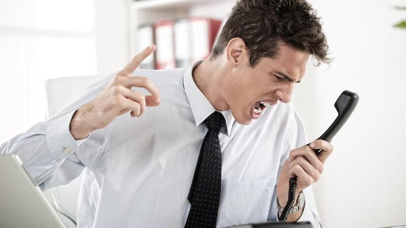Gestresster Geschäftsmann am Schreibtisch schreit wütend in Telefonhörer rein