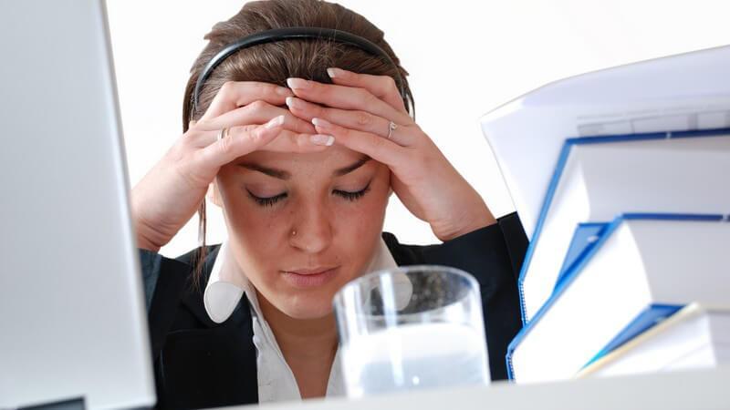 Junge dunkelhaarige Frau mit Bluse in Büro zwischen Computer und Büchern mit Wasserglas, hält sich Kopf wg Kopfschmerzen