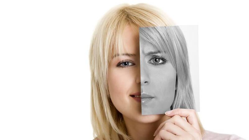 Junge Frau hält sich Foto mit ihrem Gesichtsausschnitt schwarz weiß vors Gesicht